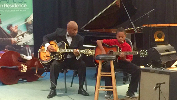 Russell Malone shares a moment with a young student at the Carr Center in Detroit, Mich. image