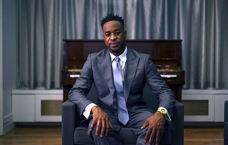 International recording artist and instrumentalist Damien Sneed seated on a piano bench with the piano behind him.
